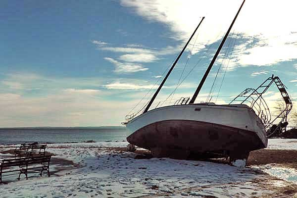 Photo of damaged boat washed up on a beach after Superstorm Sandy