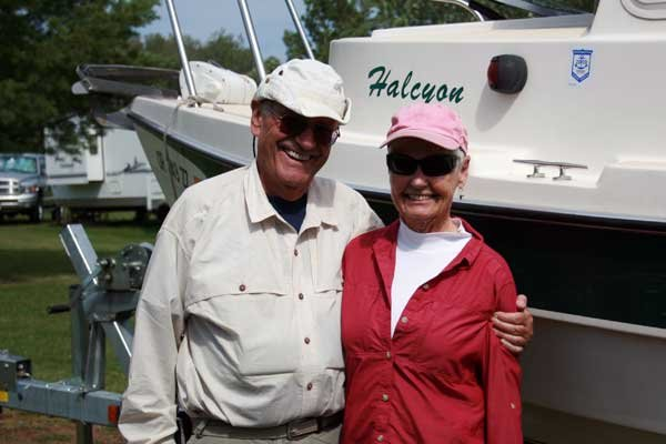 Photo of a retired couple posing in front of their boat