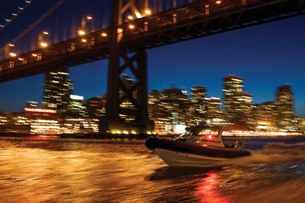 Photo of a powerboat passes beneath the Oakland-Bay Bridge with the San Francisco skyline beyond