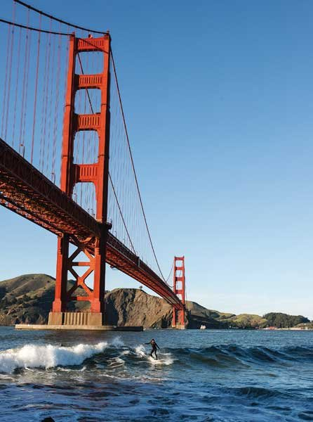 Photo of surfers in the break below the Golden Gate Bridge