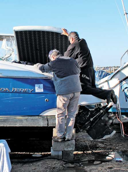 Photo of two men inspecting a boat