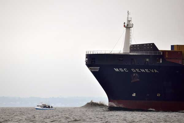 Photo of a large container ship with a small boat near it out at sea