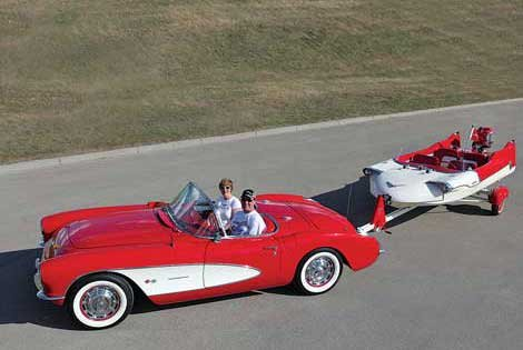 Photo of red Corvette pulling a small read boat