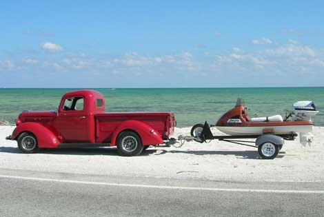 Photo of red truck towing a small boat