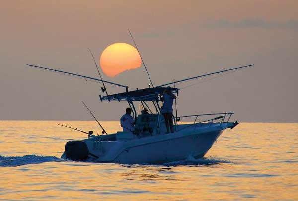 Photo of a boat on the water and Gulf Coast sunset