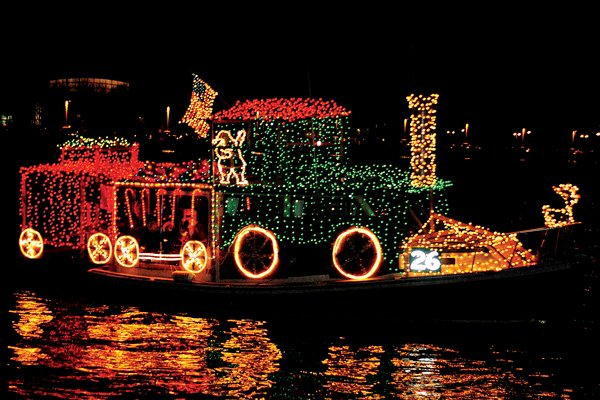 photo of boat decorated with holiday lights in the shape of a train