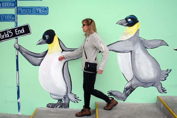 Photo of Bernadette Bernon walking in front of a penguin mural