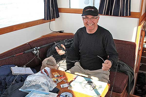 Photo of Ralph Kahal working on ling-cod rigs in the cabin of our trawler