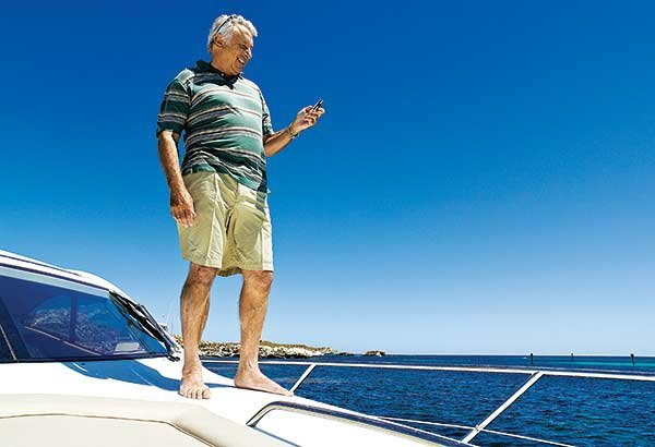 Photo of man checking smartphone on boat