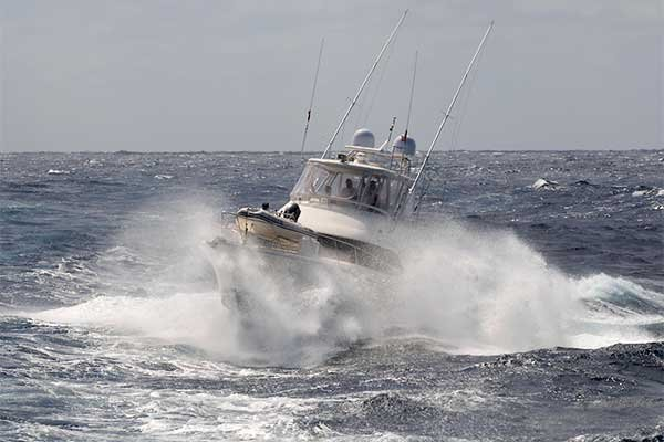 Photo of enclosed fishing boat with breaking waves