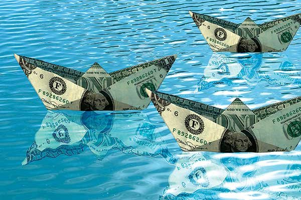 Photo of boat-shaped money floating on water