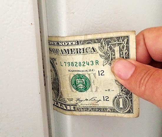 Photo of checking refrigerator seals with dollar bill