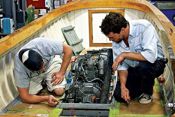 Photo of students working on boat engine systems