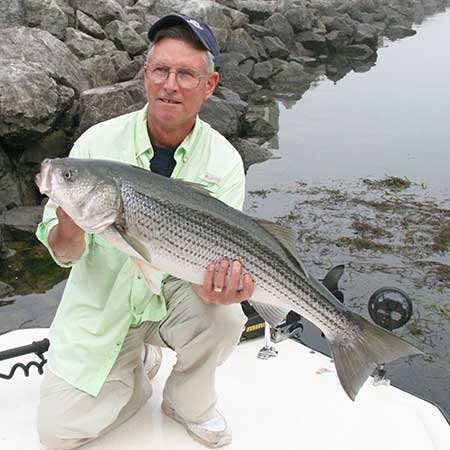 Photo of Chip Gross proudly hoisting his first Tennessee striper