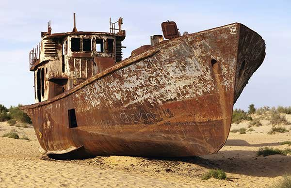 Photo of a totally corroded boat on land