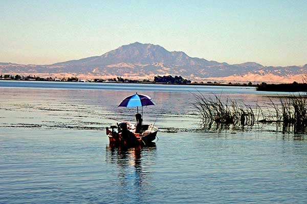 Fisherman with umbrella with Mount Diablo rising northwest