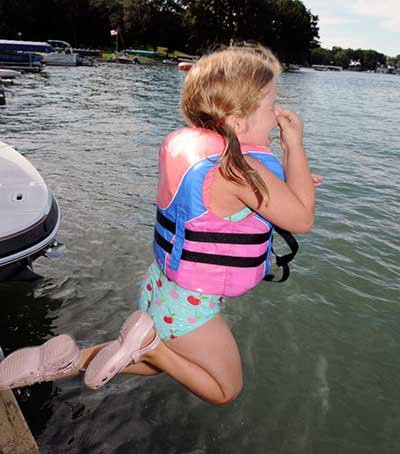 Young girl jumping off dock