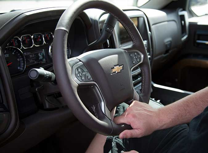 Gripping the steering wheel with one hand