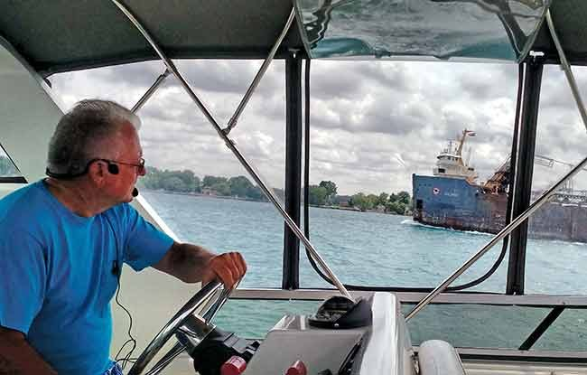 Jim Ehrman watches the commercial ships in Lake Erie from the helm