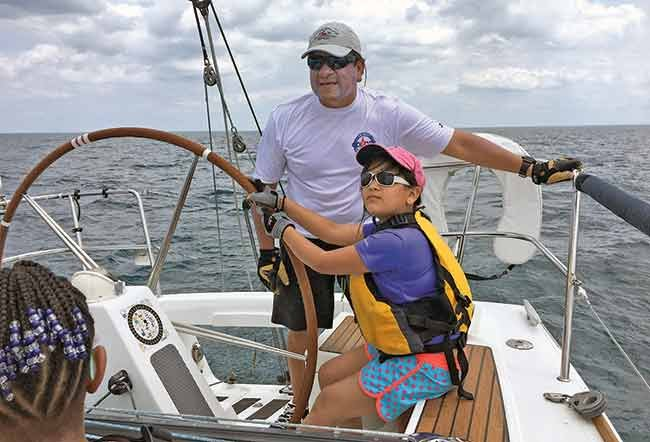 Lou Sandoval with his daughter at the helm