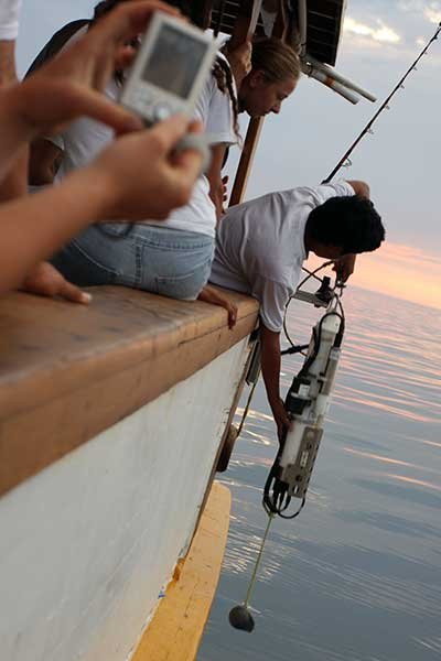 Photo of students dropping a conductivity-depth-temperature profiler off the research vessel