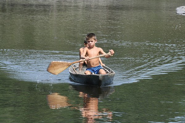 Photo of local children paddling on the Amazon River