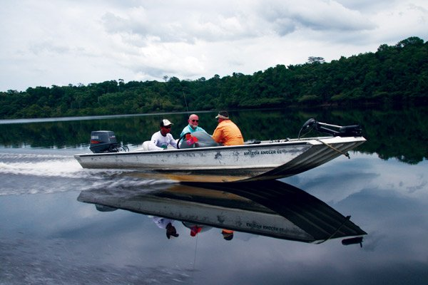 Photo of three men boating on the Amazon River