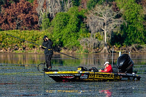 Photo of pro angler Mike Iaconelli using a push pole while fishing in a tournament