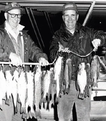 Black and white photo of Bill Nichols with a stringer of bass