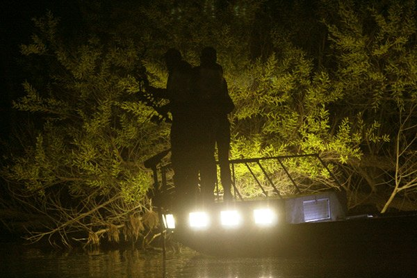 Photo of two anglers bowfishing at night