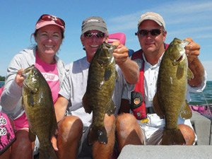 Photo of Kerry and Kevin Short and Steve Kennedy holding smallmouth bass caught on Lake Superior