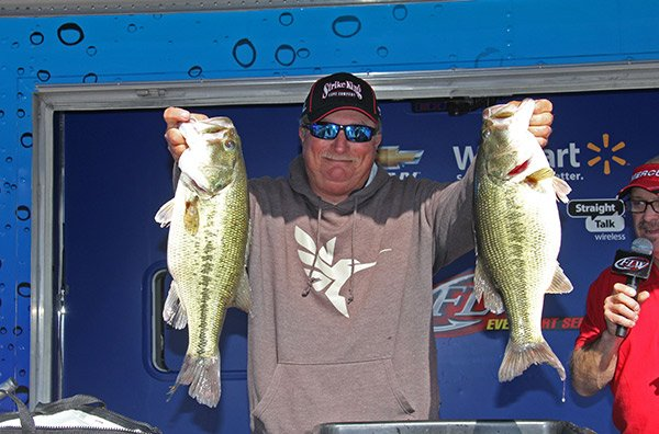 Photo of Denny Brauer holding up two bass at weigh in