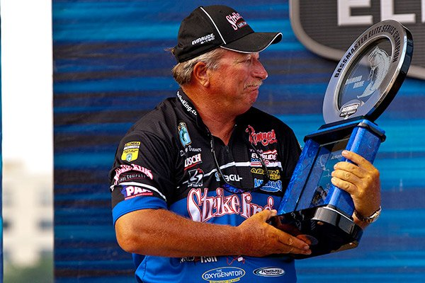 Photo of Denny Brauer with Bassmaster Elite Series trophy