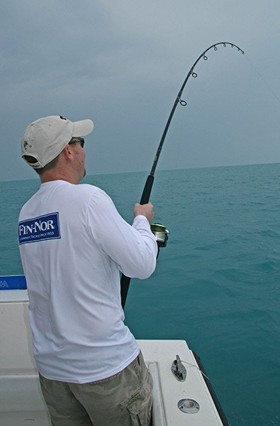Photo of a man reeling in a king mackerel