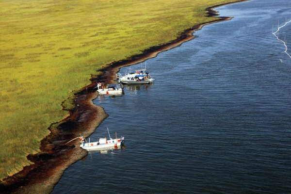 Photo of boats cleaning up oil on the Louisiana marsh.