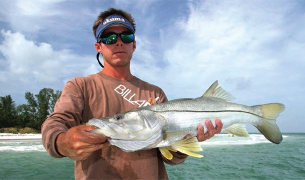 Photo of Capt. Jason Stock holding a spring snook caught in Florida waters