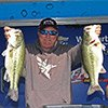 Thumbnail photo of Denny Brauer holding up two bass at weigh-in