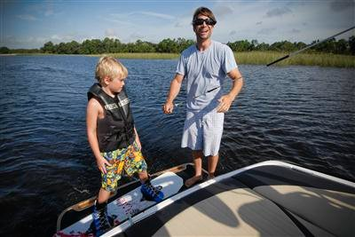 photo of Travis Moye teaching a child how to wakeboard