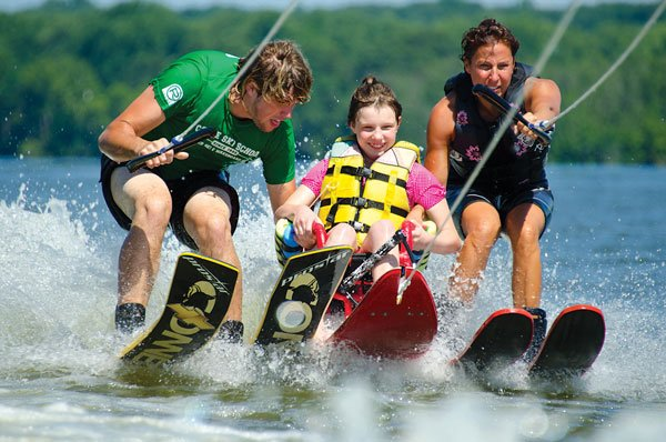 Photo of members of Dreams for Kids waterskiing with a special needs child