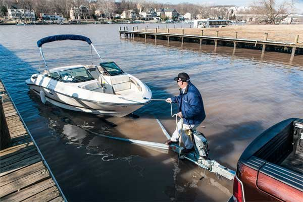 Photo of man pulling a boat back onto the ramp