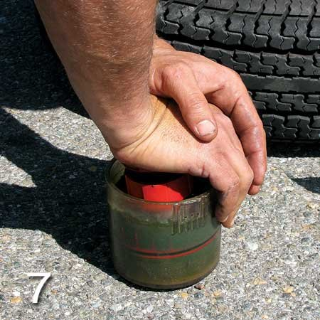 Photo of using a bearing packer to pack the inner tire hub with grease