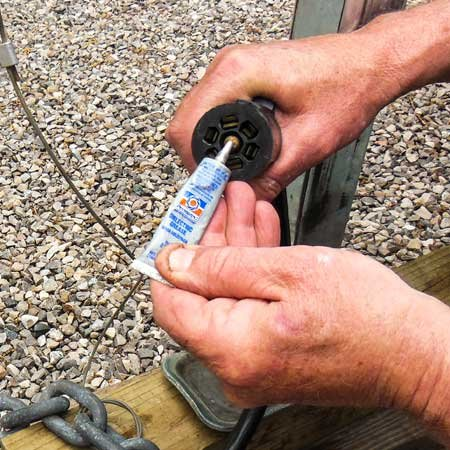 Photo of applying silicone grease to the wire harness connection