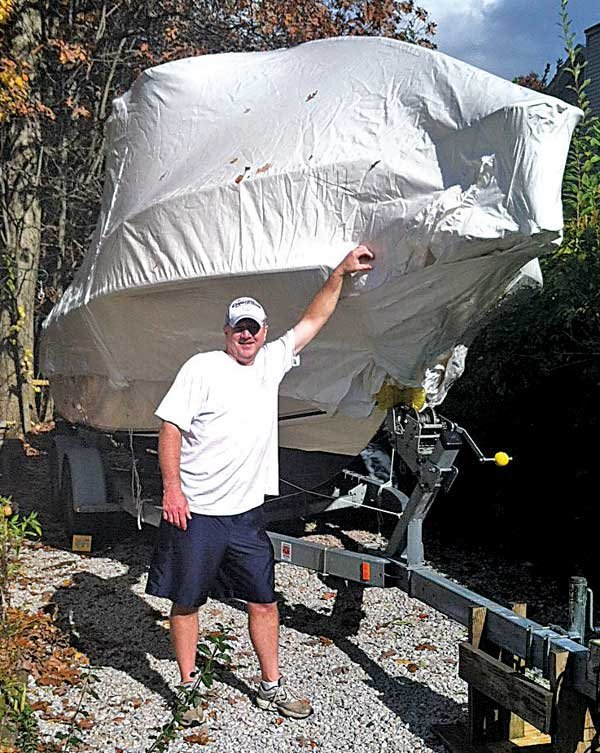 Photo of Bill Toth and his shrinkwrapped boat