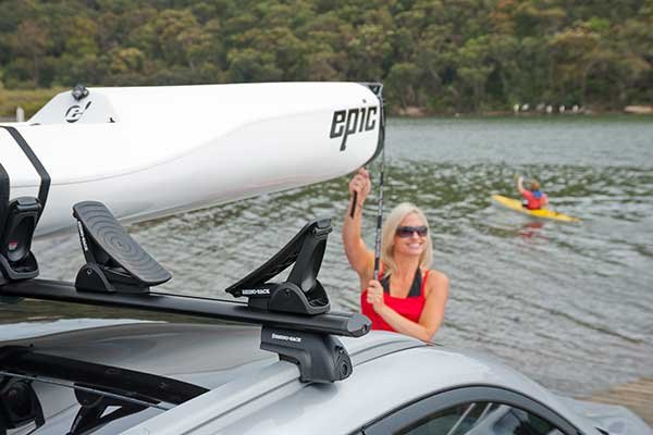 Photo of woman strapping kayak to roof rack