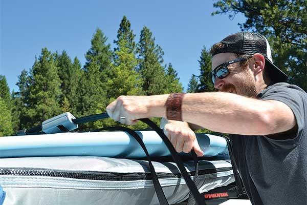 Photo of man strapping paddleboard to roof rack