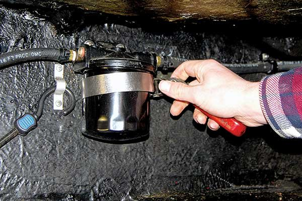 Photo of using an oil filter wrench to separate filter
