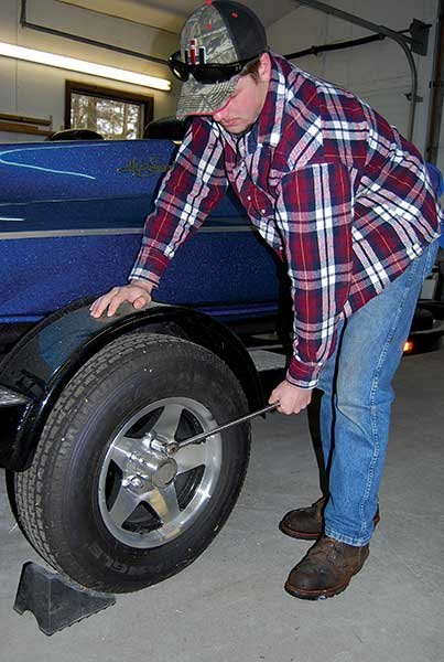Photo of man wrenching lug nuts free