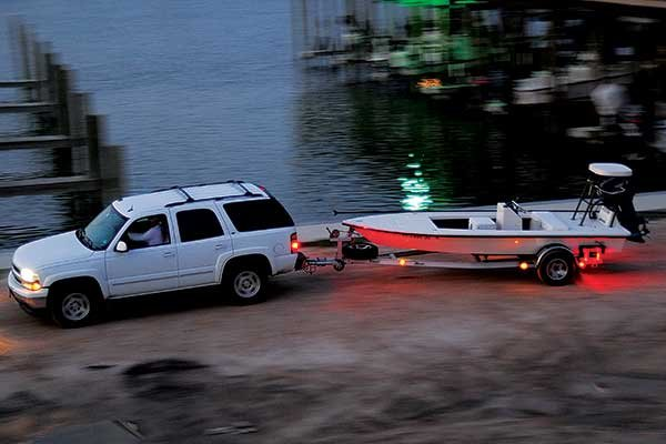 Photo of truck towing boat on trailer with lights on