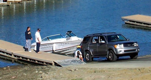Photo of three men with their boat at the ramp