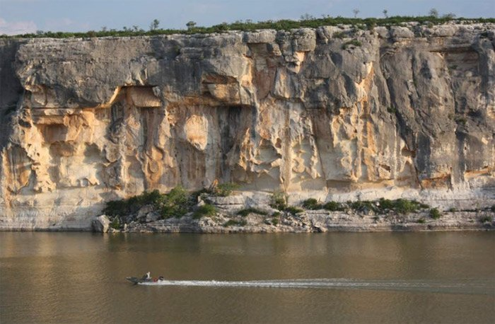 photo of anglers boating past the limestone cliffs on the Pecos River